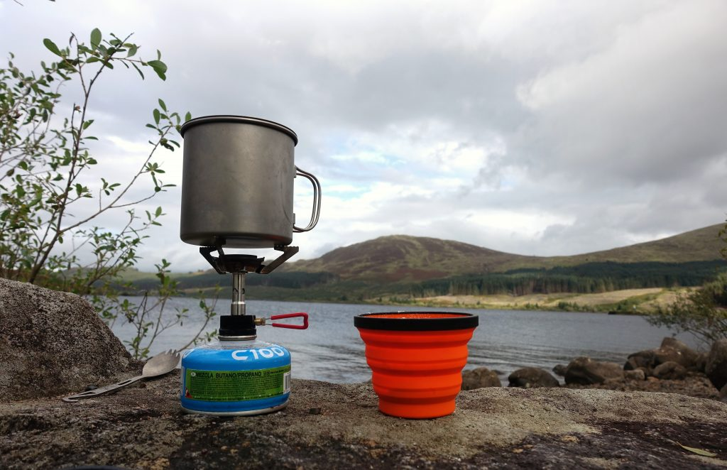 Stove and cup with a loch and hills in the background
